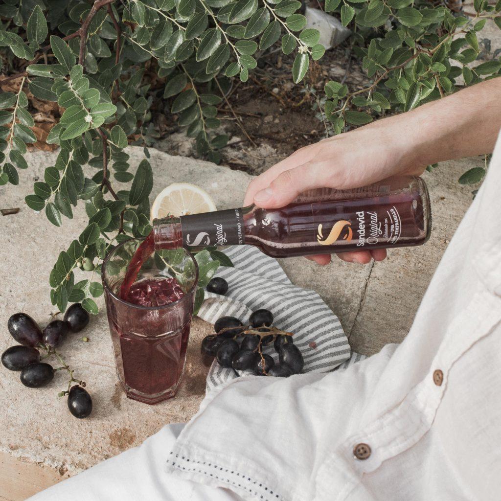 Botellín de Sandevid original junto a ingredientes naturales como la uva y el limón.