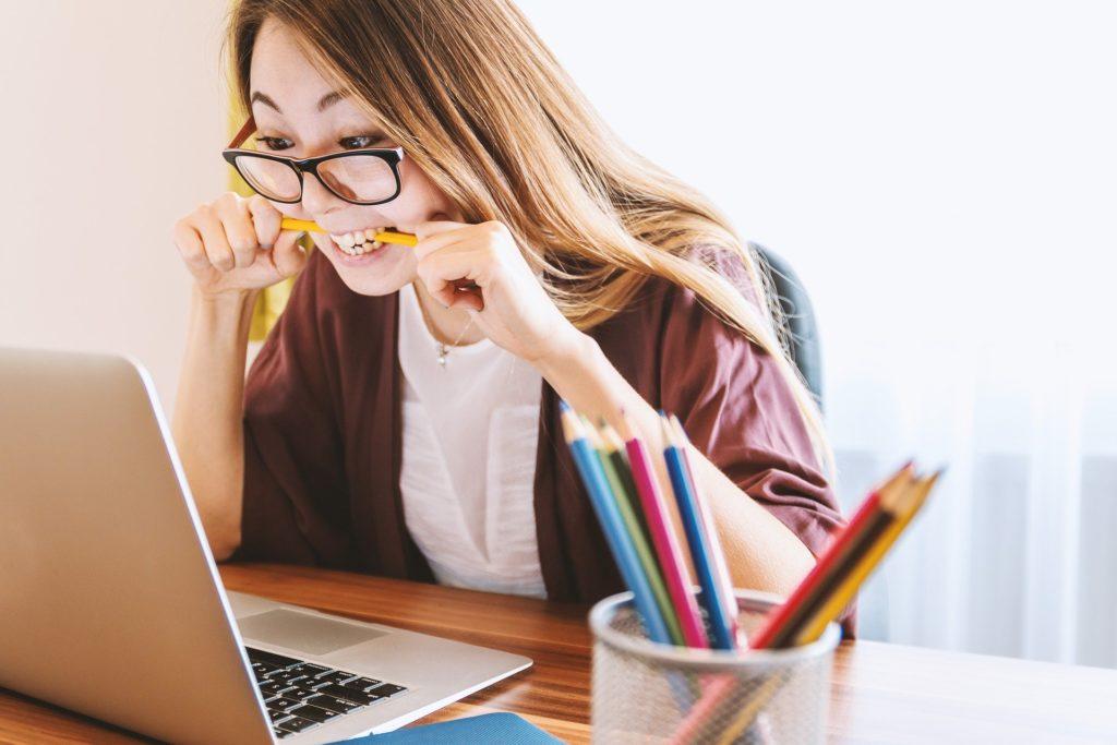 Joven histérica estudiando frente al ordenador para preparar sus exámenes.