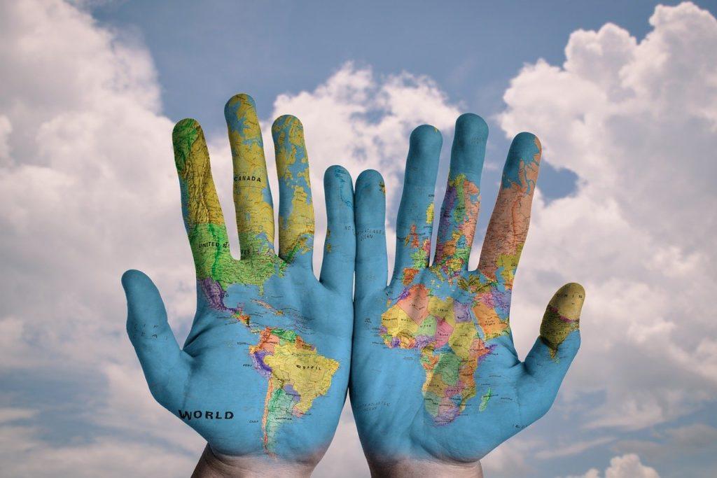 manos pintadas con un mapamundi